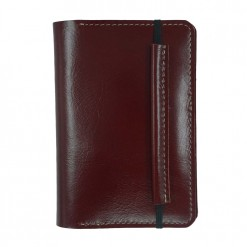 Front view of the maroon leather Mosey travel wallet with elastic clasp