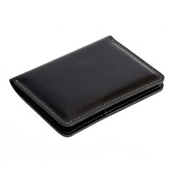 Front angled view of black Nomad leather travel wallet showing fine finishing and grain