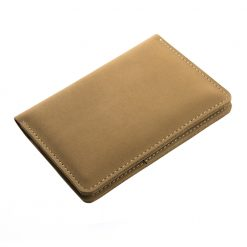 Closed angled shot of front of light brown Nomad travel wallet with fine light brown stitching
