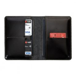 Fully open and flat view of traverse travel wallet in black with two passports inside and credit cards inserted into slots